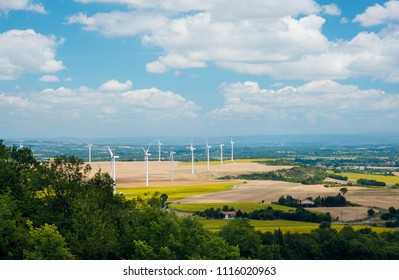 Wind turbines in France. Fields with windmills. Field in bloom. Renewable energy. Protect the environment.