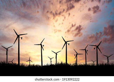 Wind turbines generate electricity during the evening. The sun goes down. Silhouettes, wind turbines, clean energy in the evening