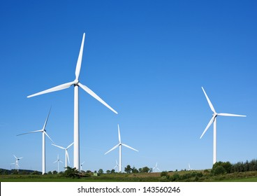 Wind turbines generating electricity against blue sky