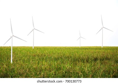 Wind turbines generating electricity on the green grass