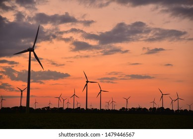 Wind turbines for generating green electricity at dusk with intense afterglow under a cloudy sky in the Burgenland plain.