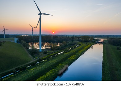 Wind turbines generating green energy during sunset as seen from above in Waalwijk, Noord Brabant, Netherlands