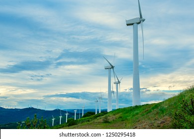 Wind turbines. Wind generators. Wind turbine generators. Alternative energy. Windmills over dramatic cloudy sky. Industrial landscape. Windmill generator. Vertical wind turbines