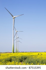 Wind turbines in a line with a blue sky in a yellow field