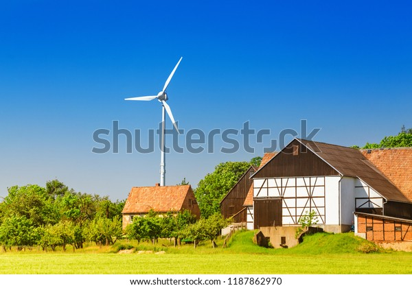 wind turbines located on farm land near crop field in the foreground. Agriculture and Sustainable energy concept