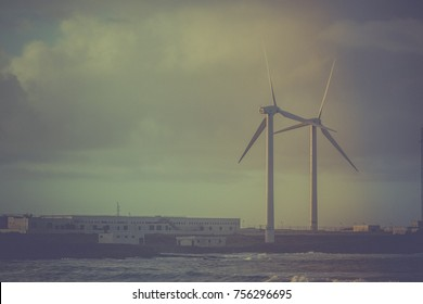 Wind turbines near factory on sky background. Color toning. Vintage. Spain, ocean panoramic view.