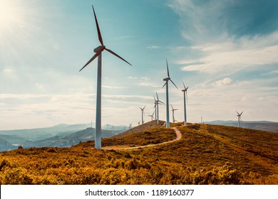 Wind turbines on beautiful sunny summer autumn mountain landsape. Curvy road through mountain Eolic park. Green ecological power energy generation. Wind farm eco field
