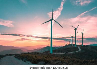 Windturbinen auf einer schönen sonnigen Sommerlila Herbstlandschaft. Kurven Straße durch den Berg Eolic Park. Ökologische Stromerzeugung aus umweltfreundlicher Energie. Öko-Feld für Windparks