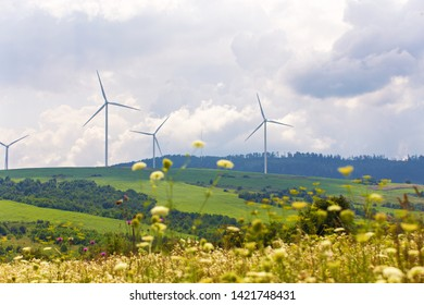 Wind turbines on beautiful sunny summer autumn mountain landsape. Green ecological power energy generation. Wind farm eco field with green grass and flowers. Beskidy range.