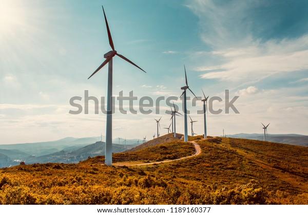 Wind turbines on beautiful sunny summer autumn mountain landsape. Curvy road through mountain Eolic park. Green ecological power energy generation. Wind farm eco field