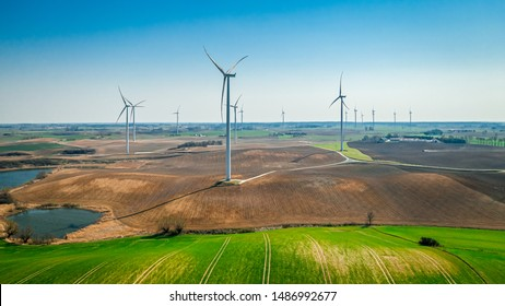 Wind turbines on brown field in spring, Poland from above