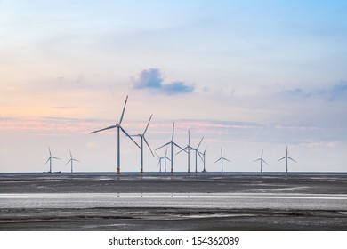 wind turbines on the coastal mud flat in sunset