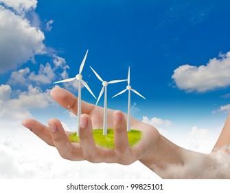 Wind turbines on hand over blue sky