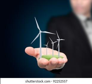 Wind turbines on the hands businessman.