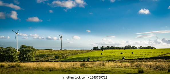 Wind turbines on the hill and rolls of hay, wrapped in black plastic, sitting in a field at South Pennines above Nelson in Lancashire, England