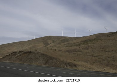 Wind Turbines on hill top with cows just below.
