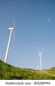 Wind turbines on hills generating electricity over a blue sky with the moon background. Clean and ecological energy production concept.