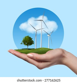 Wind turbines on meadow with tree holds in woman hand against blue sky and clouds. Green energy concept