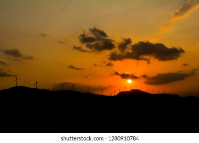 Wind turbines on mountains against the setting sun, India. Beautiful landscape. Sustainable energy source. Wind energy.