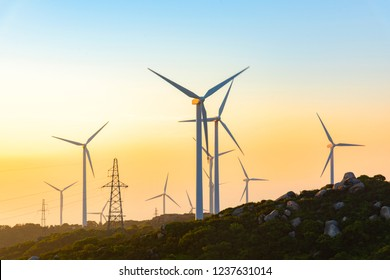Wind turbines on the mountains are on the beach at sunrise and sunset.