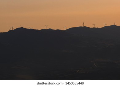 Wind turbines on the top of the mountains in Tuscany - Italy - at sunset