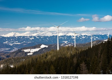 Wind turbines on a wooded ridge in front of snowy mountains of the Styrian Alps under blue sky.