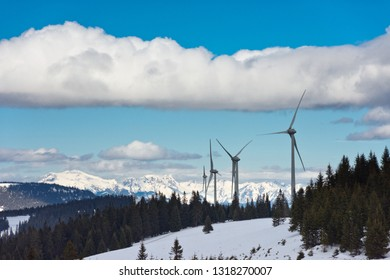 Wind turbines on a wooded ridge in front of snowy mountains of the Styrian Alps under blue sky with big cloud.