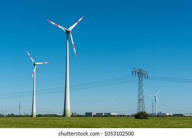 Wind turbines and overhead lines on a sunny day seen in Germany