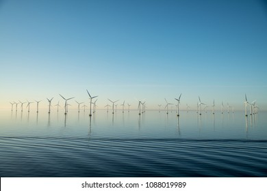 Wind turbines park in the water in Oresund outside Malmo - Sweden in sunrise with calm ocean and small ripples