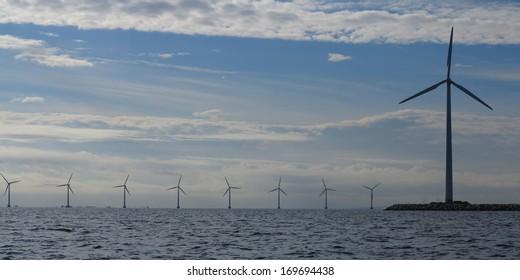 wind turbines power generator farm for renewable energy production along coast baltic sea near Denmark. Alternative green clean energy, ecology.