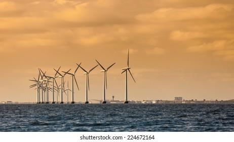 wind turbines power generator farm for renewable energy production along coast baltic sea near Denmark at sunset or sunrise. Alternative green energy ecology.