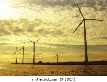 wind turbines power generator farm for renewable energy production along coast baltic sea near Denmark at sunset /sunrise. Alternative green energy. ecology.