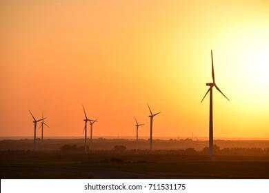 Wind turbines producing clean renewable energy on North Dakota prairie at sunset.