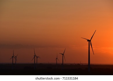 Wind turbines producing clean renewable energy on North Dakota prairie at sunset.