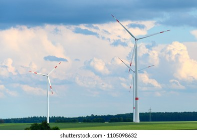 Wind turbines providing sustainable energy and electricity in a rural landscape against a cloudy blue sky