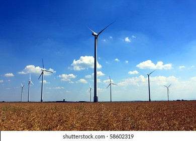 wind turbines rapeseed field in summer blue sky white clouds
