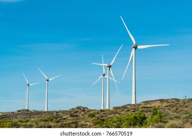 Wind turbines in a rocky mountains in Portugal over a deep blue sky. Renewable energy ecological concept