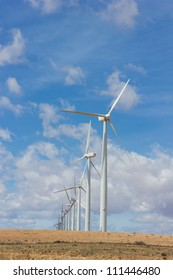 Wind turbines in a row against cloudy sky