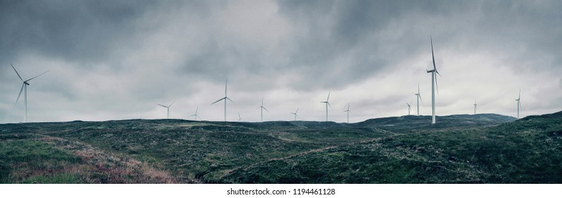 Wind Turbines in the Scottish Highlands - panoramic view of wind turbines dotted along a bleak, barren landscape in the Scottish wilderness.