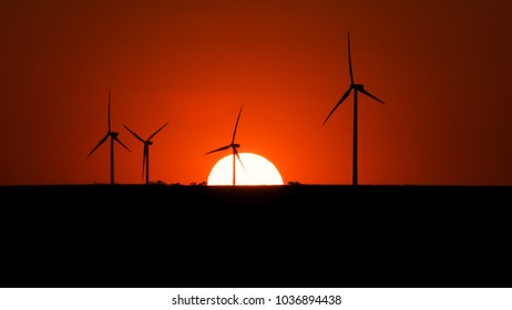Wind turbines silhouettes on sunset background