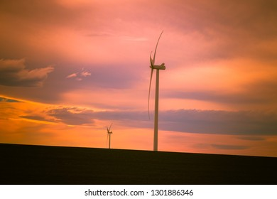 Wind turbines sit lonely in a shadow-covered field against a beautiful sunset sky, generating renewable energy for the State of Idaho.