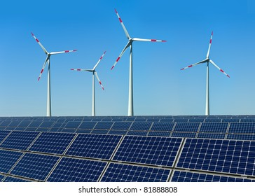 Wind turbines and solar panels against a blue sky