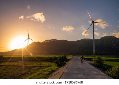 Wind turbines and solar panels in a big green field at sunset to generate renewable clean energy