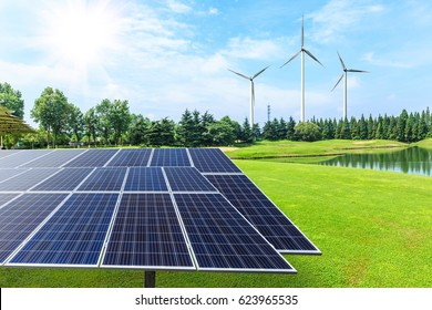 Wind turbines and solar panels on green field