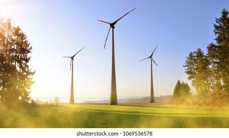 Wind turbines in spring landscape at sunrise. Concept of clean energy.