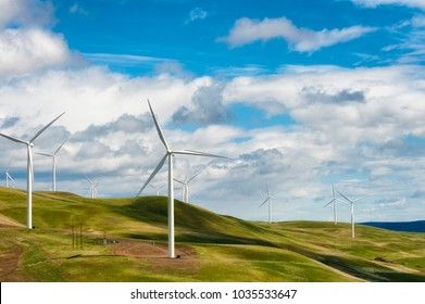Wind Turbines stand tall and stark against the high desert landscape of rolling hills in the Columbia River Gorge