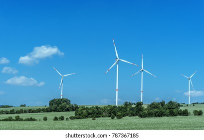 wind turbines standing on field with lush green grass