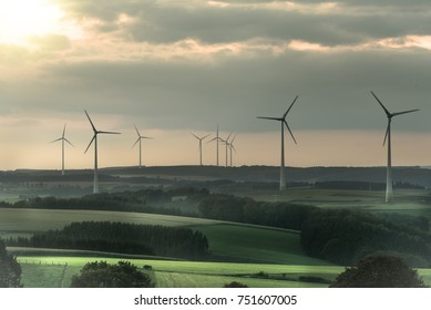 Wind turbines standing tall in front of a beautiful sunset sky. Representing clean energy as the power source of the future. Struggle against global warming. Hosingen, Oesling in Luxembourg.