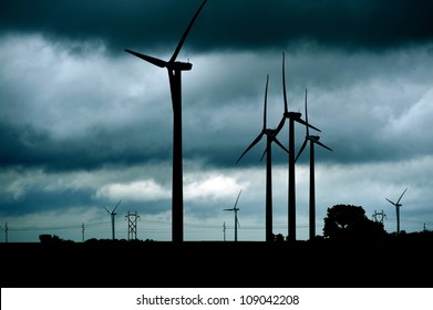 Wind Turbines Stormy Theme. Dark Stormy Theme with Many Wind Turbines Landscape. Technology Photo Collection.