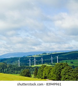 Wind turbines in summer green mountains